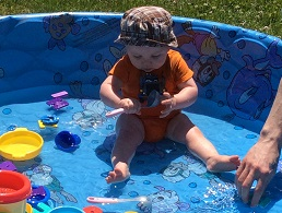Baby with hat playing with toys in blue wadding pool.