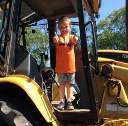 Smiling child standing in a construction vehicle with two thumbs up