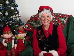 Mrs Carol Claus posing with elves