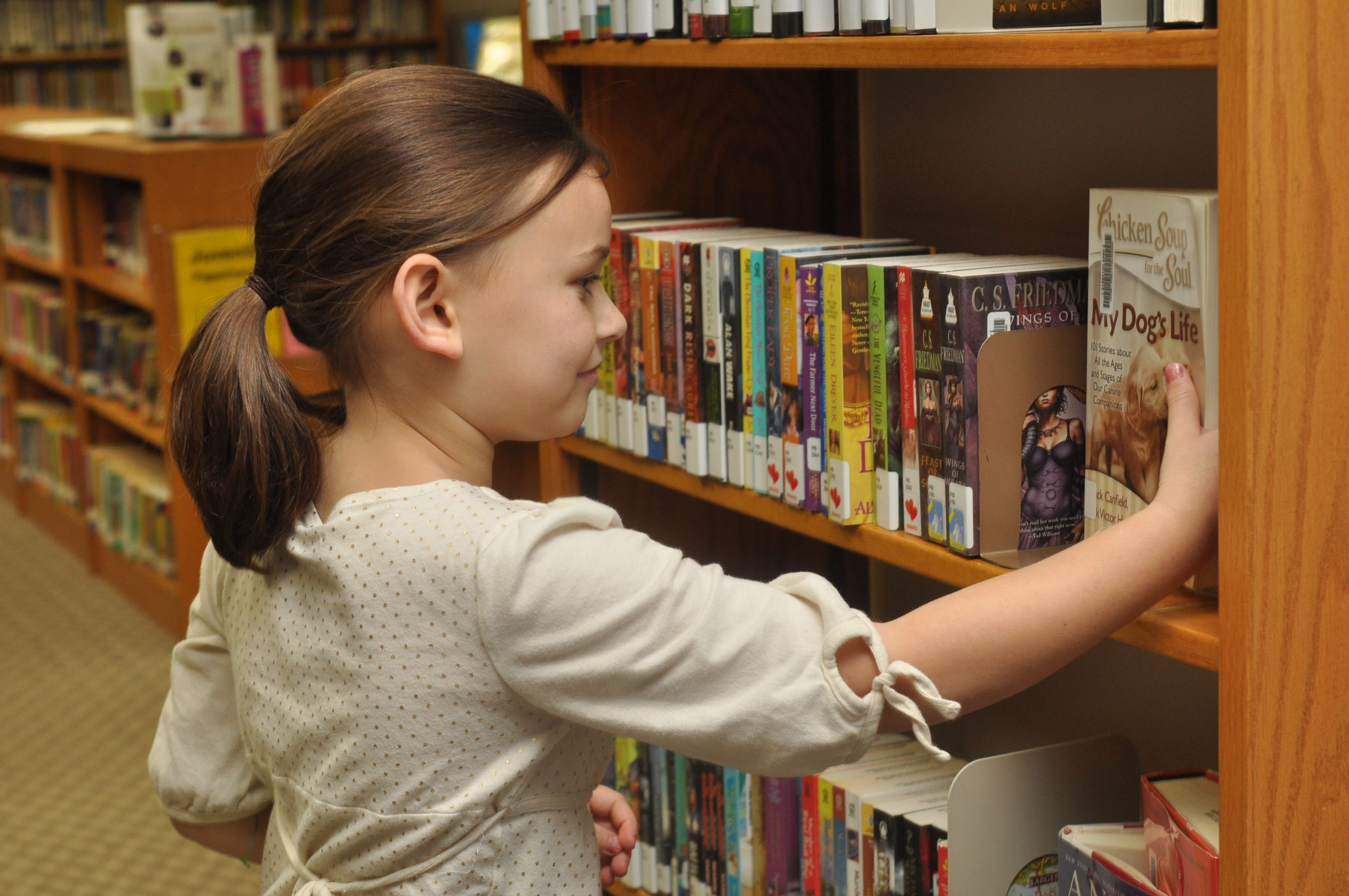 Young girl looking at books on a library bookshelf