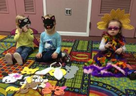 Children on Story rug wearing different masks