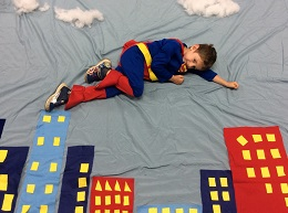 Child dressed as superhero flying over buildings